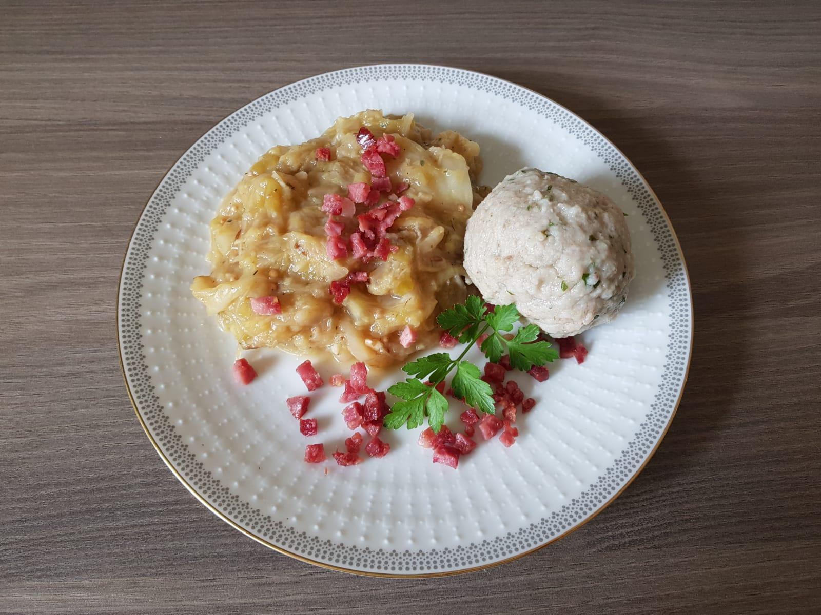 Selbstgemachte Kartoffelknödel mit Kraut und Speck